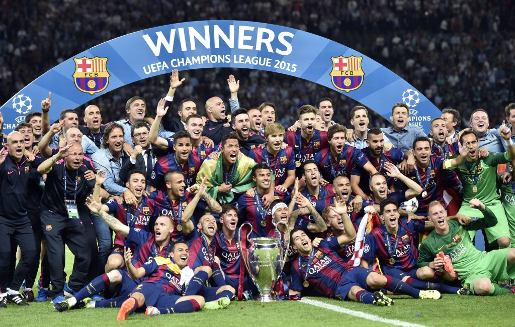 Barcelona team and staff celebrate with the trophy after winning 3-1 the Champions League final soccer match between Juventus Turin and FC Barcelona at the Olympic stadium in Berlin Saturday, June 6, 2015. (AP Photo/Martin Meissner)